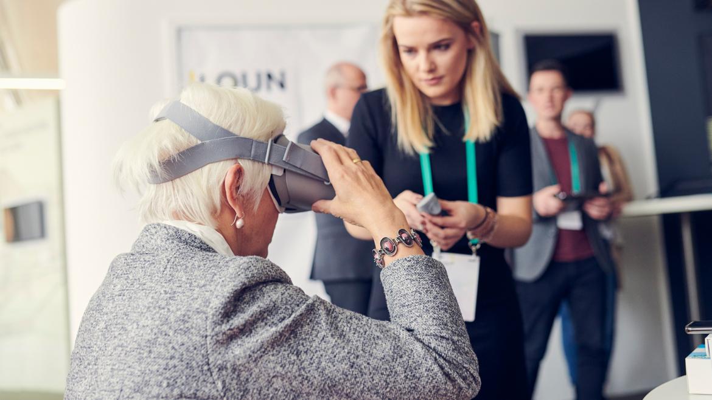 Im Vordergrund eine ältere Frau mit VR-Brille, dahinter eine junge Frau, die erklärt. Im Bildhintergrund eine Gruppe von Menschen.