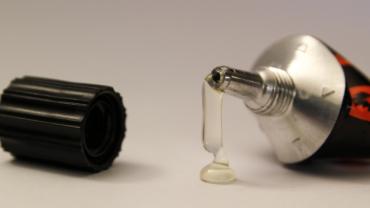 Das Bild zeigt eine geöffnete Klebstofftube, aus der Klebstoff austritt.