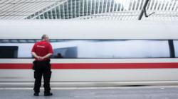 Mann in Security Uniform steht an Bahnhof, ein weißer ICE mit rotem Streifen fährt vorbei