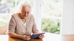 Das Themenbild Ambient Assisted Living zeigt eine Seniorin mit einem Tablet-PC.