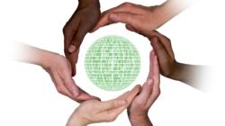 Das Themenbild Digitale Partizipation zeigt eine digitale Erdkugel umgeben von vielen Händen.