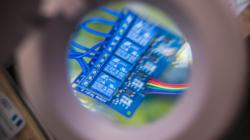 Das Themenbild IoT und Sensorik zeigt die innere Elektronik eines Sensors unter einer Lupe.