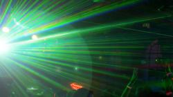 Das Themenbild Licht und Laser zeigt einen grünen Laser geteilt an einer Disco-Kugel.