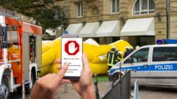 Das Themenbild Öffentliche Sicherheit zeigt einen Polizeieinsatz und ein Smartphone, auf dem eine App eine Warnung dazu auflistet.