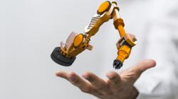 Das Themenbild Robotik zeigt einen kleinen Roboterarm, der über einer Hand schwebt.