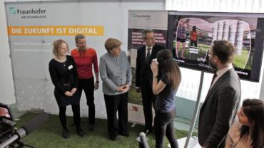 Bundeskanzlerin Angela Merkel steht vor dem Fraunhofer-Stand und lässt sich das Exponat erklären.