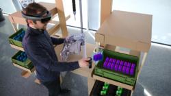 Foto eines Menschen, der an einem aufgebauten Montagearbeitsplatz steht und dort digital erzeugte Montagearbeiten vornimmt