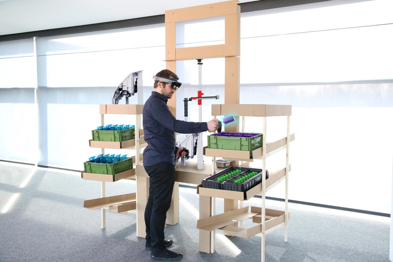 Foto eines Mannes am Cardboard, an dem reale und über AR sichtbare Montageelemente zur Testen des Ablaufs vorliegen.