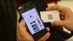 Auf einem Smartphone werden bunt eingefärbte Blöcke dargestellt, um die Position in der Blockchain zu verdeutlichen.