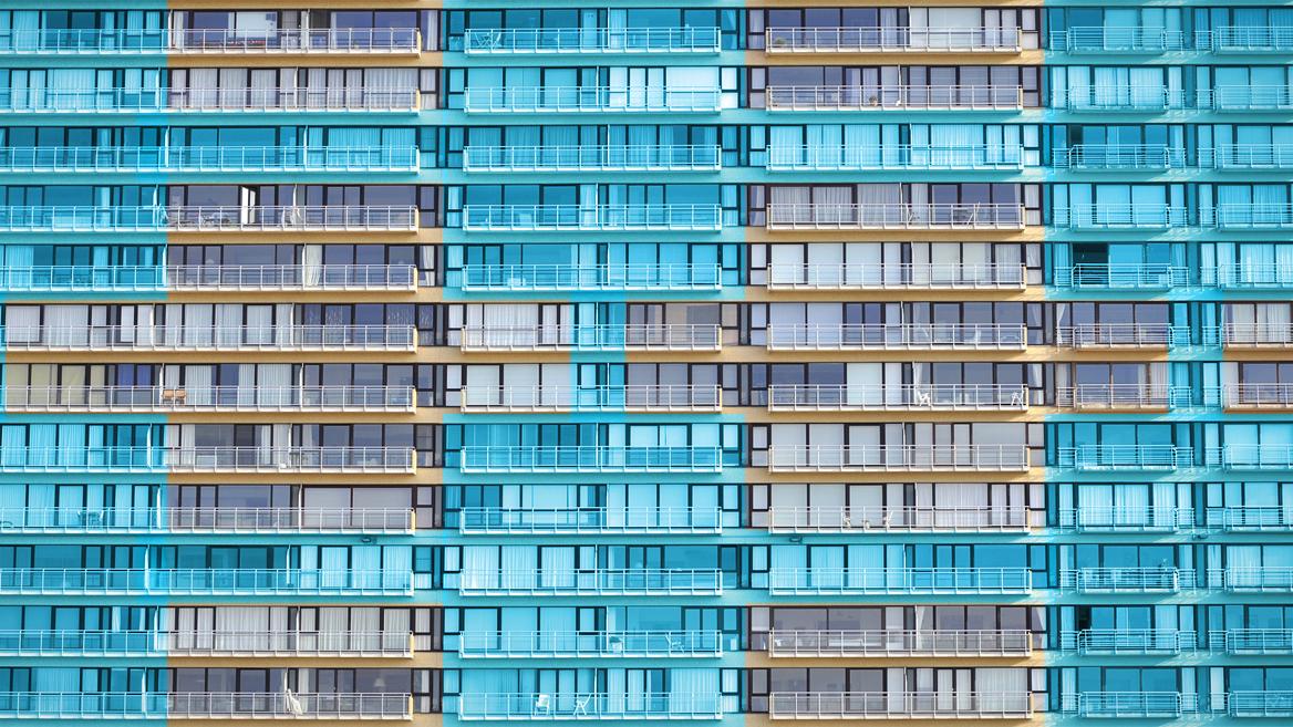 Die Fassade eines sehr großen, mehrstöckigen Wohnhaus, die gleichförmig aussieht und so die einzelnen Blöcke der Blockchain symbolisiert und mit menschlichen Identitäten verbindet.